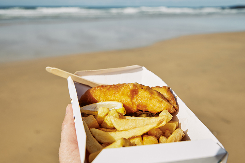 POV of a hand holding a box of Fish and Chips at the beach on a bright sunny day.