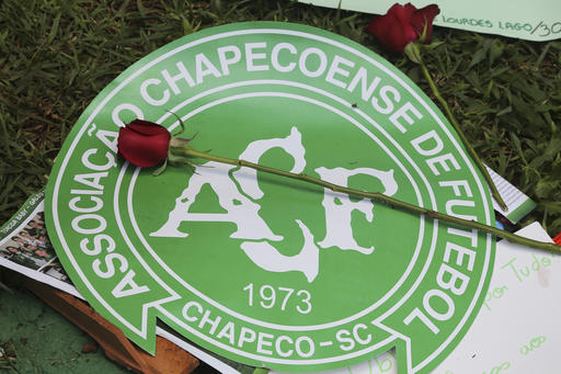 A red rose sits on top of the Chapecoense soccer team logo outside the Arena Conda stadium, where team fans are gathering in Chapeco, Brazil, Tuesday, Nov. 29, 2016. A chartered plane that was carrying the Brazilian soccer team Chapecoense to the biggest match of its history crashed into a Colombian hillside and broke into pieces, Colombian officials said Tuesday. (AP Photo/Andre Penner)