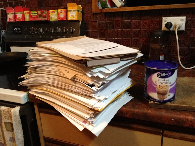 A stack of paper, with convenient tin of hot chocolate for size comparison.