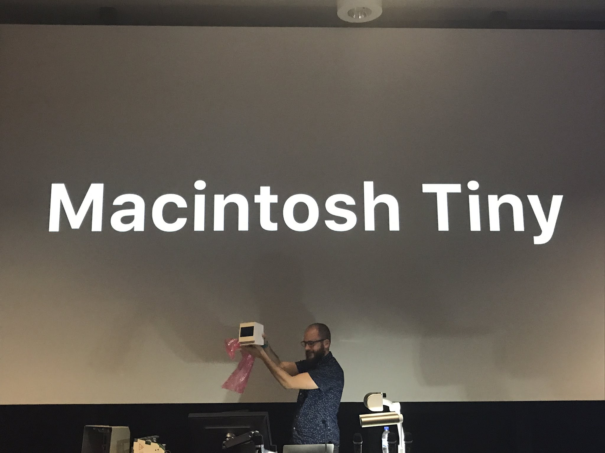 "Photo of me, holding the Macintosh Tiny, at /dev/world 2017, in front of projected text ""Macintosh Tiny"""