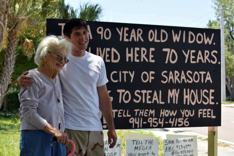Marie and Miles standing in front of the sign. Image via HeraldTribune.