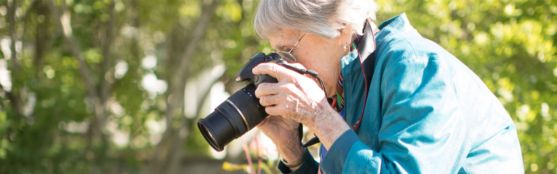 Senior women taking pictures with camera outside