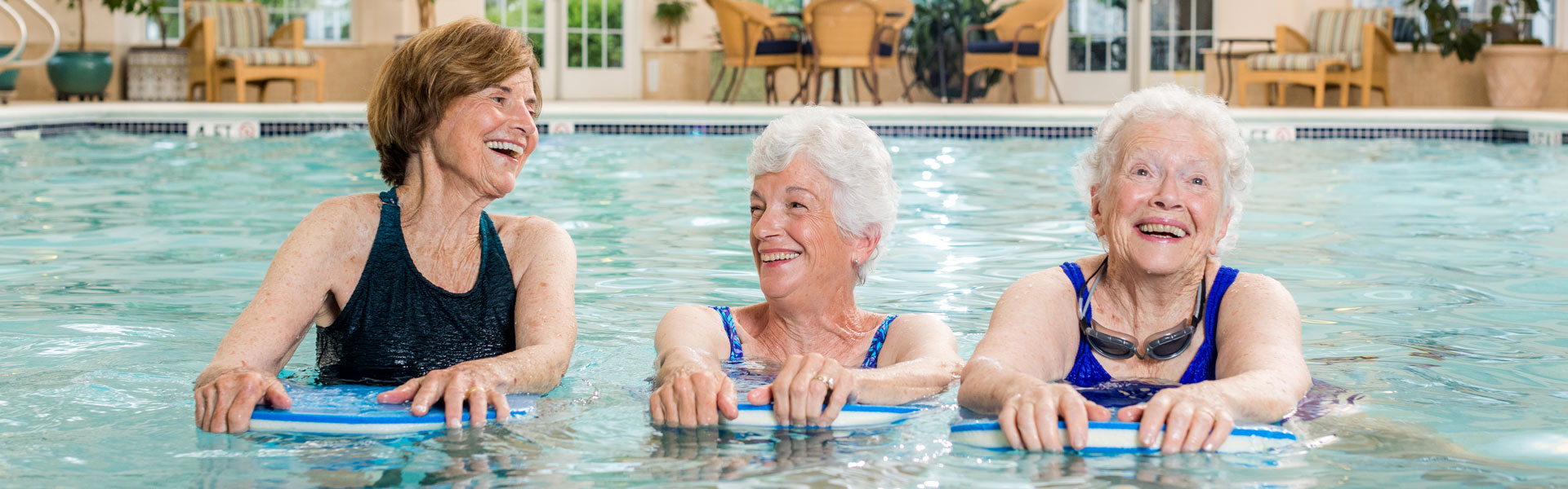Three senior women swimming in pool at StoneRidge Senior Independent Living