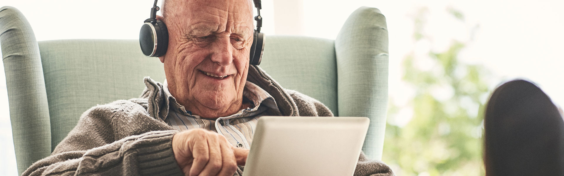 Senior man with headphones using digital tablet
