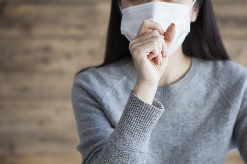 Woman wearing a mask has a cough
