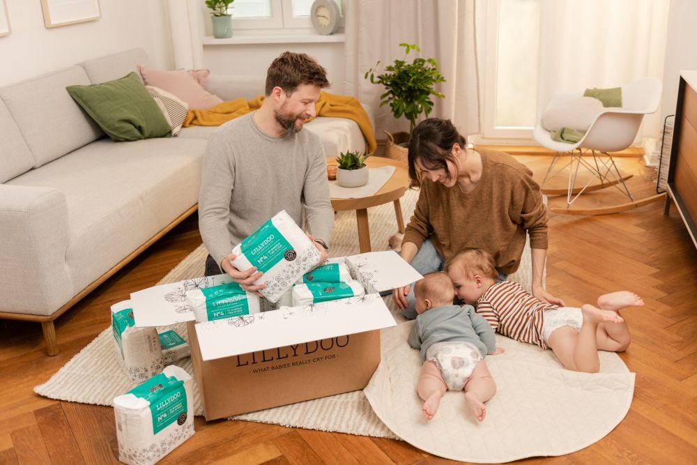 Eltern packen mit ihren beiden Babys die Testbox von LILLYDOO aus.