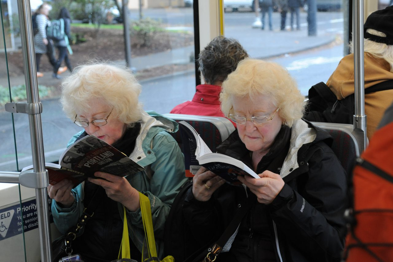 Two women reading books on Portland Streetcar