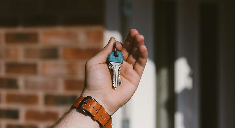 Hand holding a pair of keys in front of a door