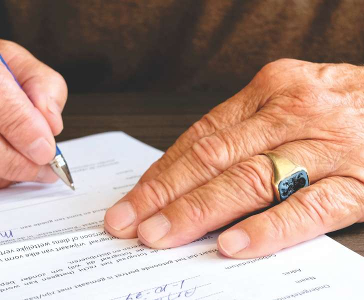 Elderly man signing a contract