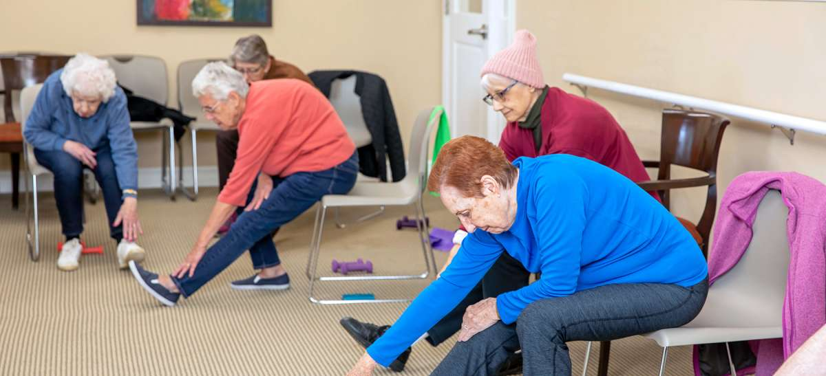 Senior woman stretching before taking a fitness class at their New York senior living community