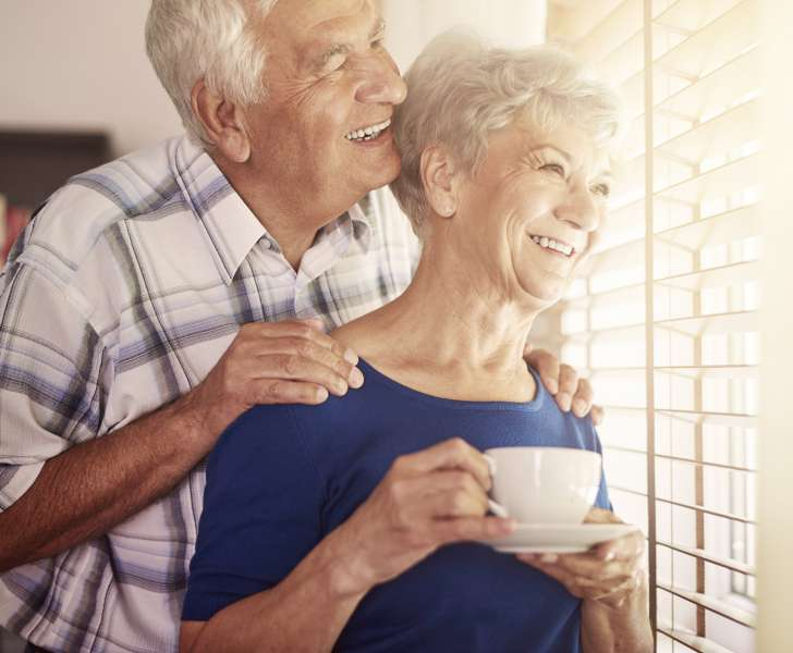 Elderly couple smiling and looking out a window