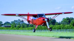 A red Short Wing Piper flying over the runway.