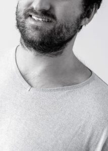 Cropped portrait of a man with a beard.