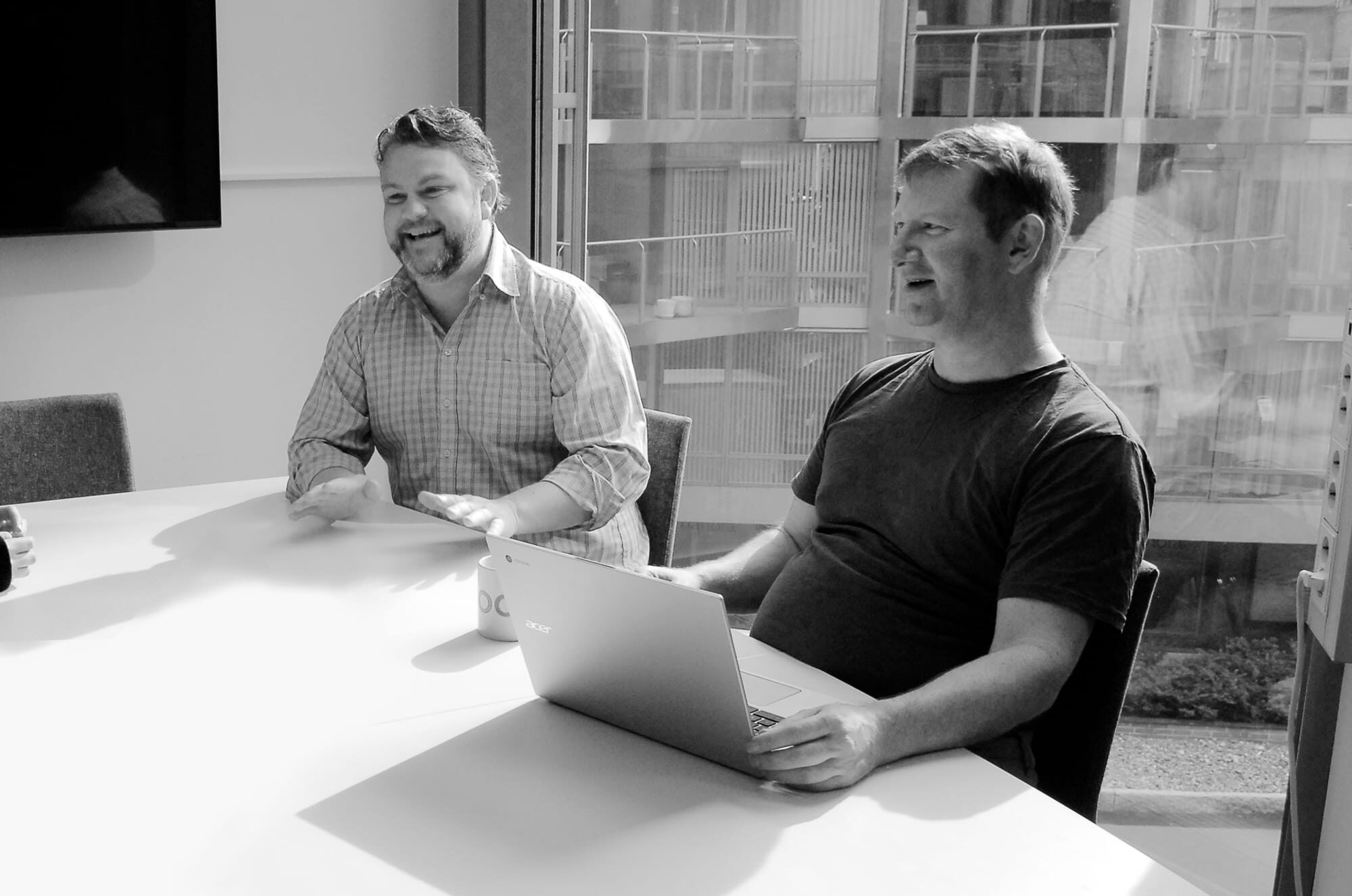 Two smiling male The Cloud People employees in a meeting.