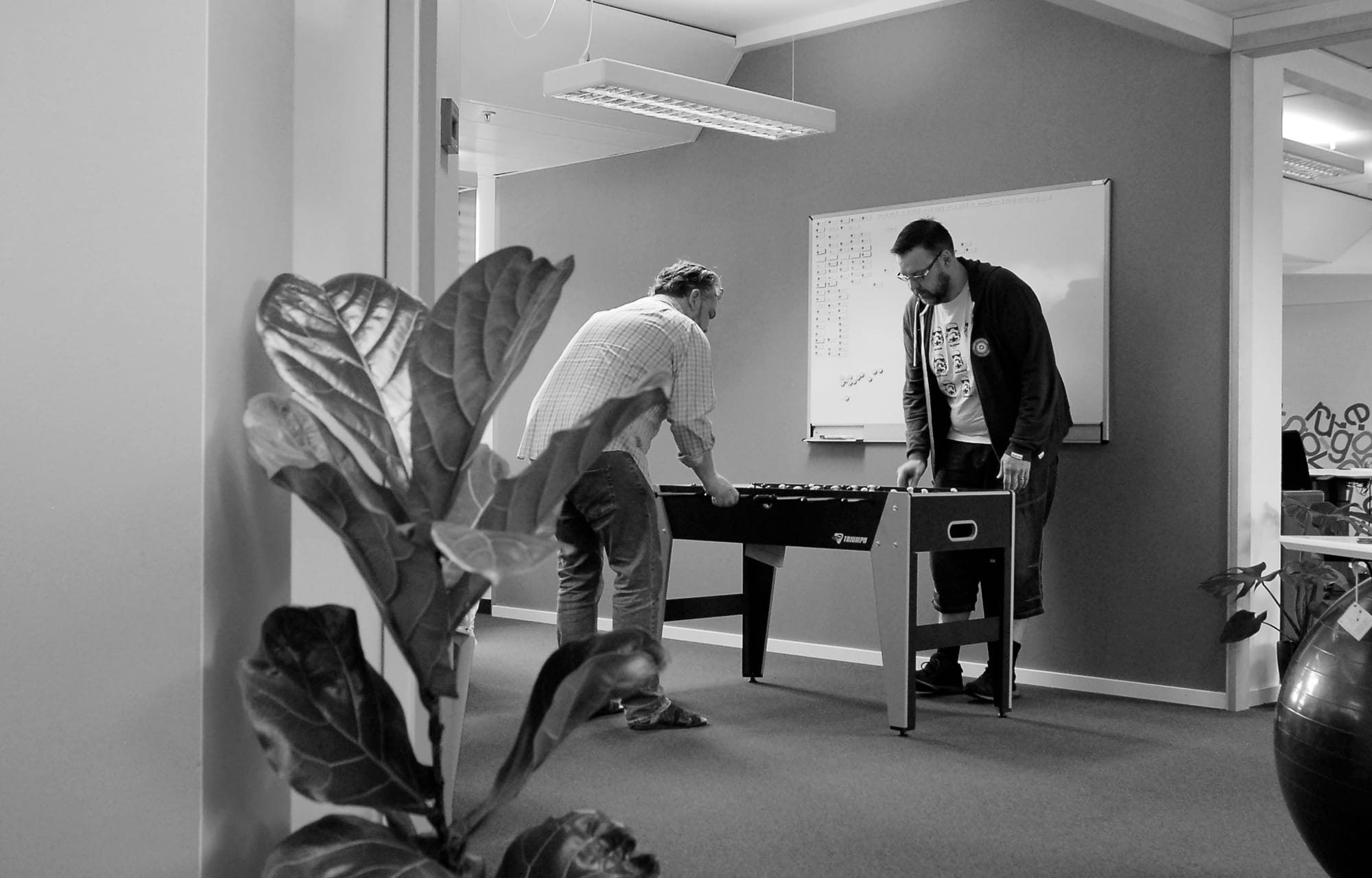 Two employees at The Cloud People playing fussball in the office.