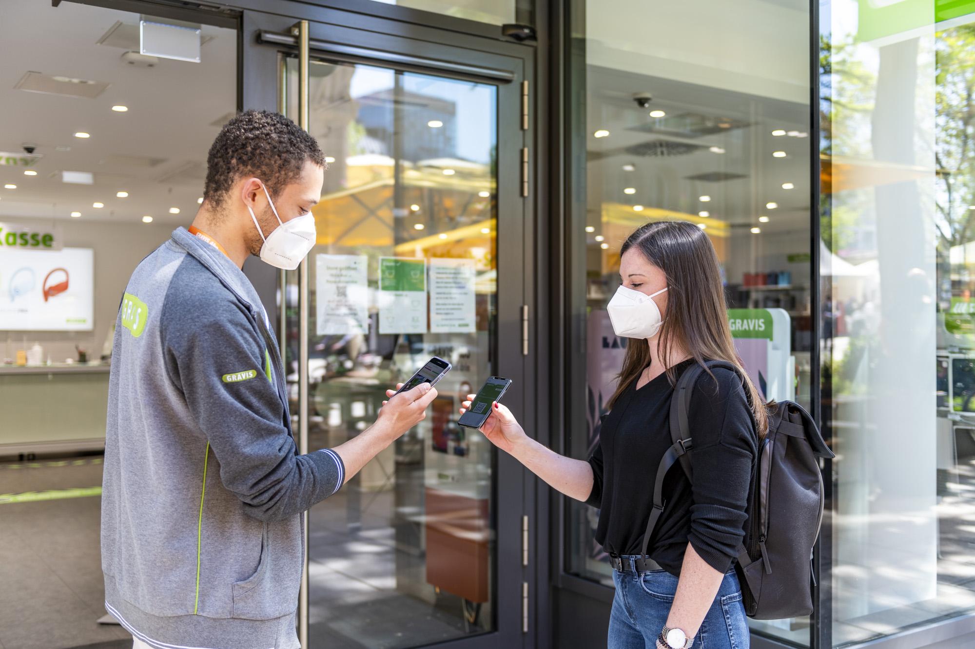 Ein Gravis Mitarbeiter scannt die Wallet Karte einer Kundin mit smartervisit im Rahmen von Click & Meet Vorgaben.