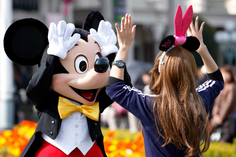 The Walt Disney Co. character Mickey Mouse greets a visitor at Tokyo Disneyland, operated by Oriental Land Co., in Urayasu city, Chiba prefecture, Japan, on Friday, April 15, 2011. Tokyo Disneyland opened earlier than its 8 a.m. schedule today as about 10,000 people lined up to visit the amusement park that had been shut by the strongest earthquake on record to hit Japan. Photographer: Kiyoshi Ota/Bloomberg