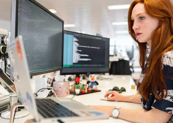 Uma mulher ruiva em frente a duas telas de computador. Em uma das telas, um terminal de computador está aberto.