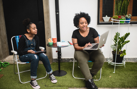 Duas pessoas estão em um jardim com uma grama verde. Do lado esquerdo, uma adolescente com um macacão jeans, tênis branco e branco, blusa preta está sentada em uma cadeira colorida. Ao lado dela, uma mesa pequena preta com um caderno em cima e copos. Do lado direito, uma mulher com uma blusa preta com manga, calça verde escura está com um notebook no colo, olhando fixamente para ele e sorrindo. Ao fundo, plantas em vasos coloridos.
