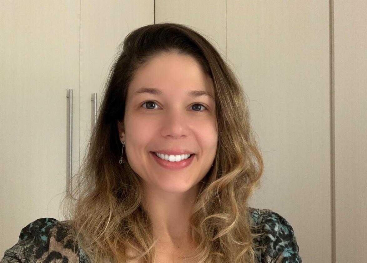 Uma mulher com cabelo loiro bem sorridente olhando para a câmera, ela está usando uma blusa com uma estampa de onça. Atrás dela, tem um guarda-roupa claro.