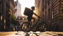 Um ciclista atravessa uma rua, ele carrega uma mochila de entregador e usa um capacete. Ao fundo a luz do sol delinea a sua silhueta.