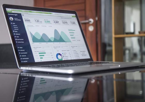 Um notebook aberto da cor prateado em cima de uma mesa. Na tela, dois gráficos e métricas de dados impressas nas cores verde e preto. Ao fundo da imagem, uma porta semi-aberta e um armário.