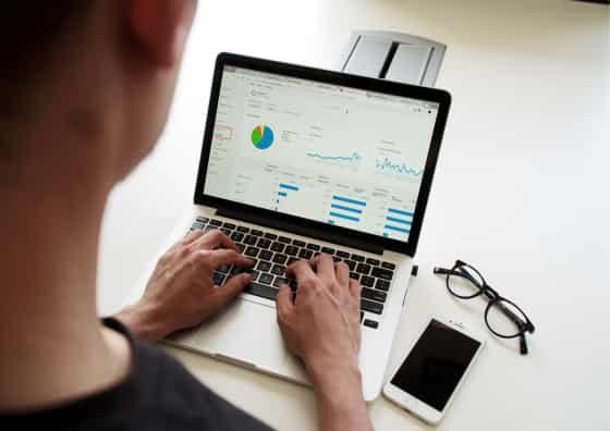 Um homem de costas com uma camisa preta está com as mãos em um notebook. Na tela do notebook temos gráficos e diagramas. Do lado do notebook um óculos com armação na cor preta e um celular.