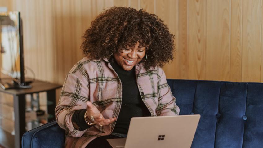 Uma mulher sentada em um sofá da cor azul escuro segura um notebook em seu colo. Uma das mãos está um pouco levantada e a outra está no notebook. Ela está vestindo uma blusa de frio de cor marrom com listas pretas. Ao fundo, uma parede de madeira e uma mesa do lado esquerdo com objetos de escritório.