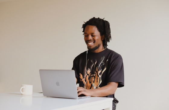 Um homem com uma camisa preta está sentado em frente a uma mesa. Ele está sorrindo e com um fone de ouvido. Suas mãos estão digitando em um notebook prateado. Ao lado do notebook, um caneta de cor branca.