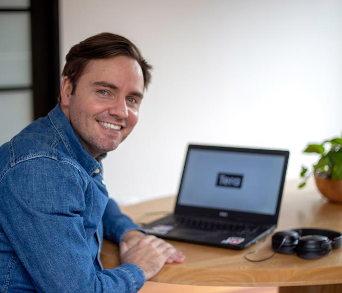 Um homem de óculos segura um notebook preto, enquanto mexe no trackpad. Ele usa uma camiseta verde musgo, um óculos quadrado e prata. Tem barba. Ao fundo, desfocado, um homem observa uma parede com vários postits, rosas e laranjas, colados.