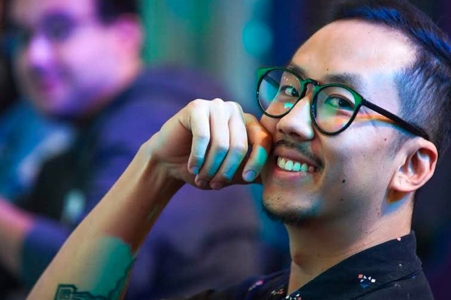 A foto foca no rosto de um homem. Ele tem traços asiáticos, sorri e sua mão encosta no queixo, perto da boa. Usa óculos e camiseta preta.