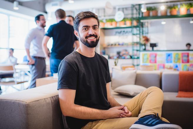 Um homem sentado no sofá, veste uma camiseta preta, calça bege e usa tênis. Ele sorri para câmera. Ao fundo é possível observar um lounge.