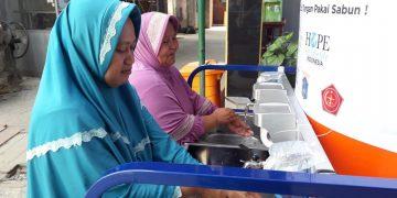 Ibu-ibu sedang mencuci tangan di wastafel keliling