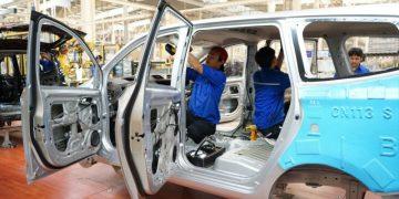 lustrasi pabrik sedang memproduksi mobil