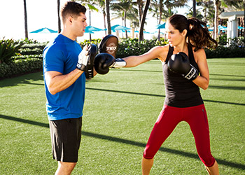 A woman in boxing gloves with trainer