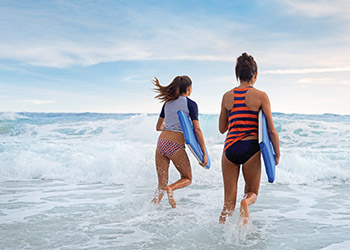 Two girls with shortboards entering the water