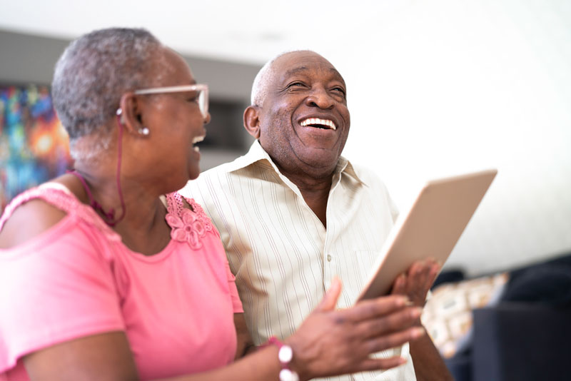 senior couple laughing while on a tablet