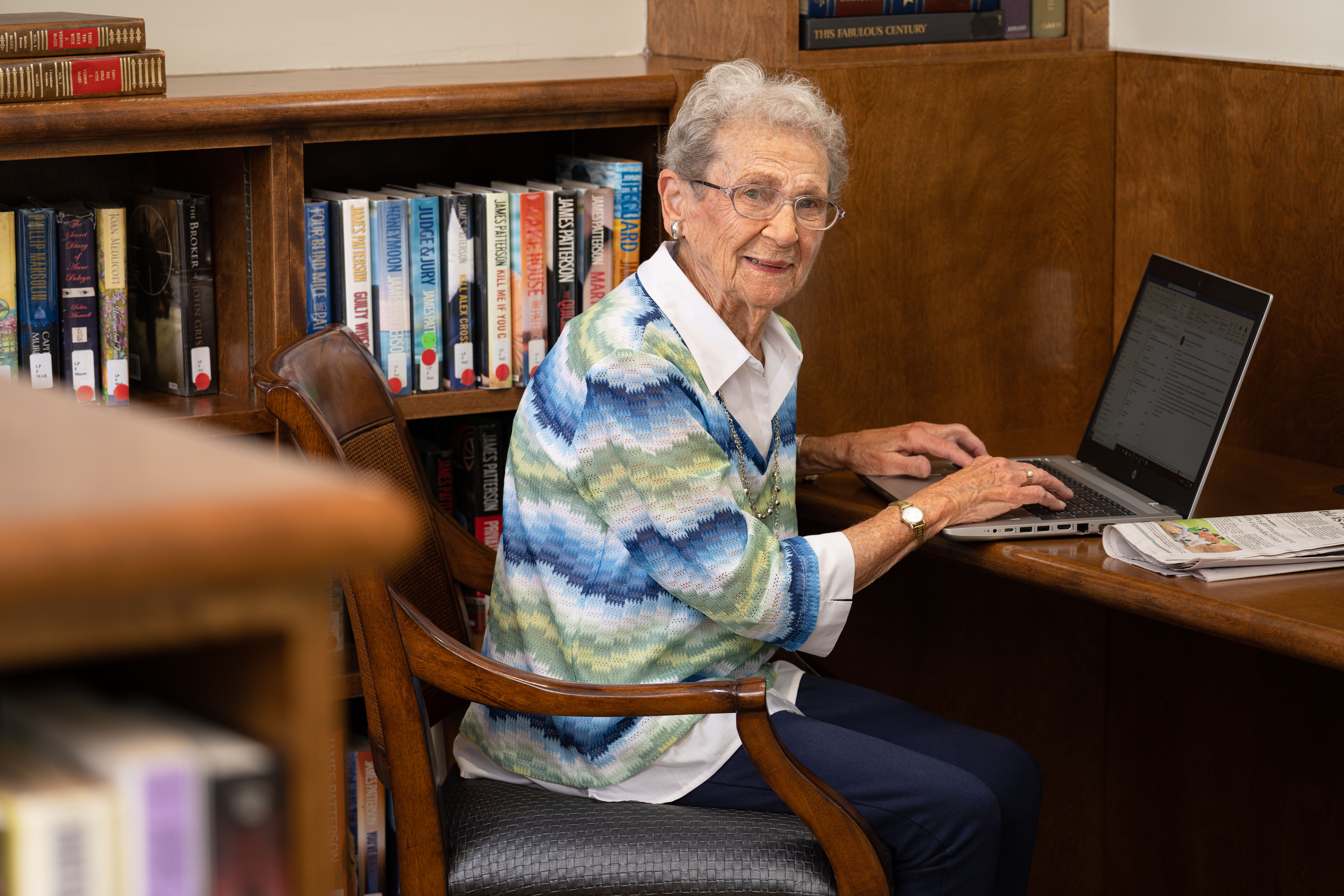 senior resident at The Chespeake on laptop in the library area