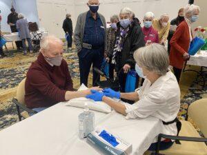 Heart Health Fair hosted by The Chesapeake. Senior woman taking senior man's pulse.