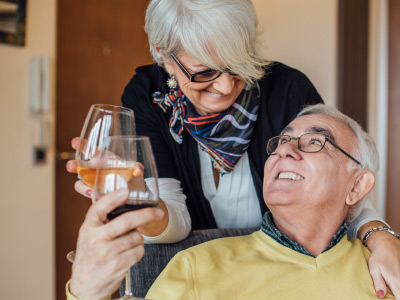 independent living couple saying cheers with wine