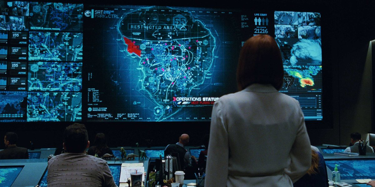 Claire observing the control room monitors displaying a map of Isla Nublar.