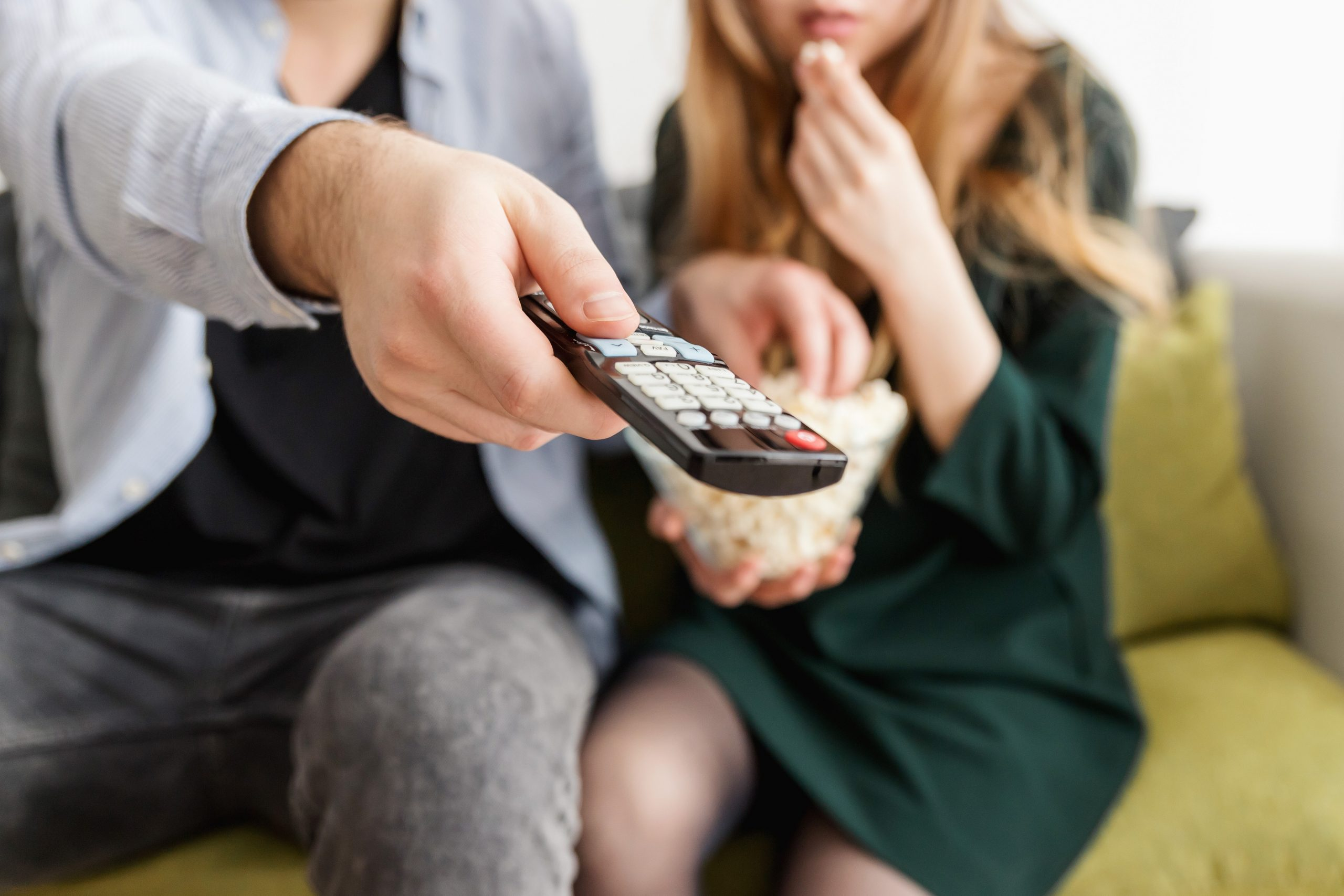 A man and a woman with a TV remote