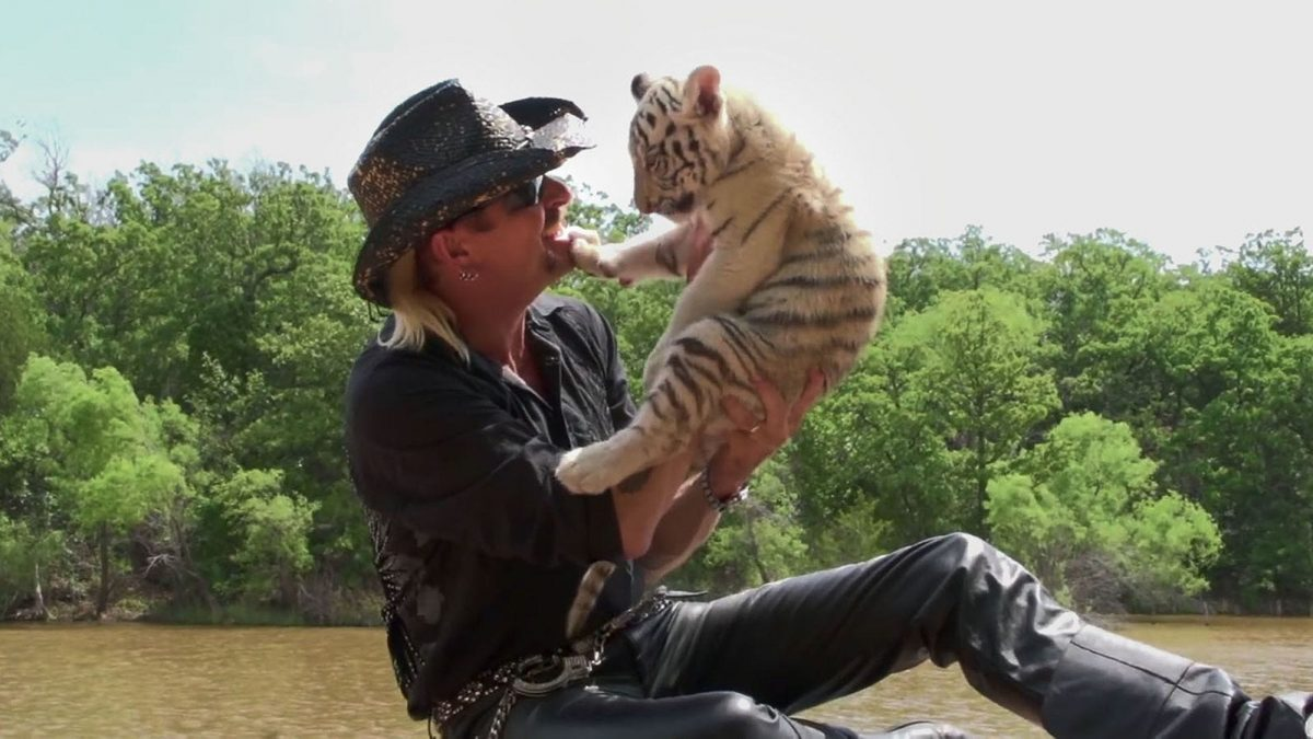 A country music video featuring a man holding a tiger cub.