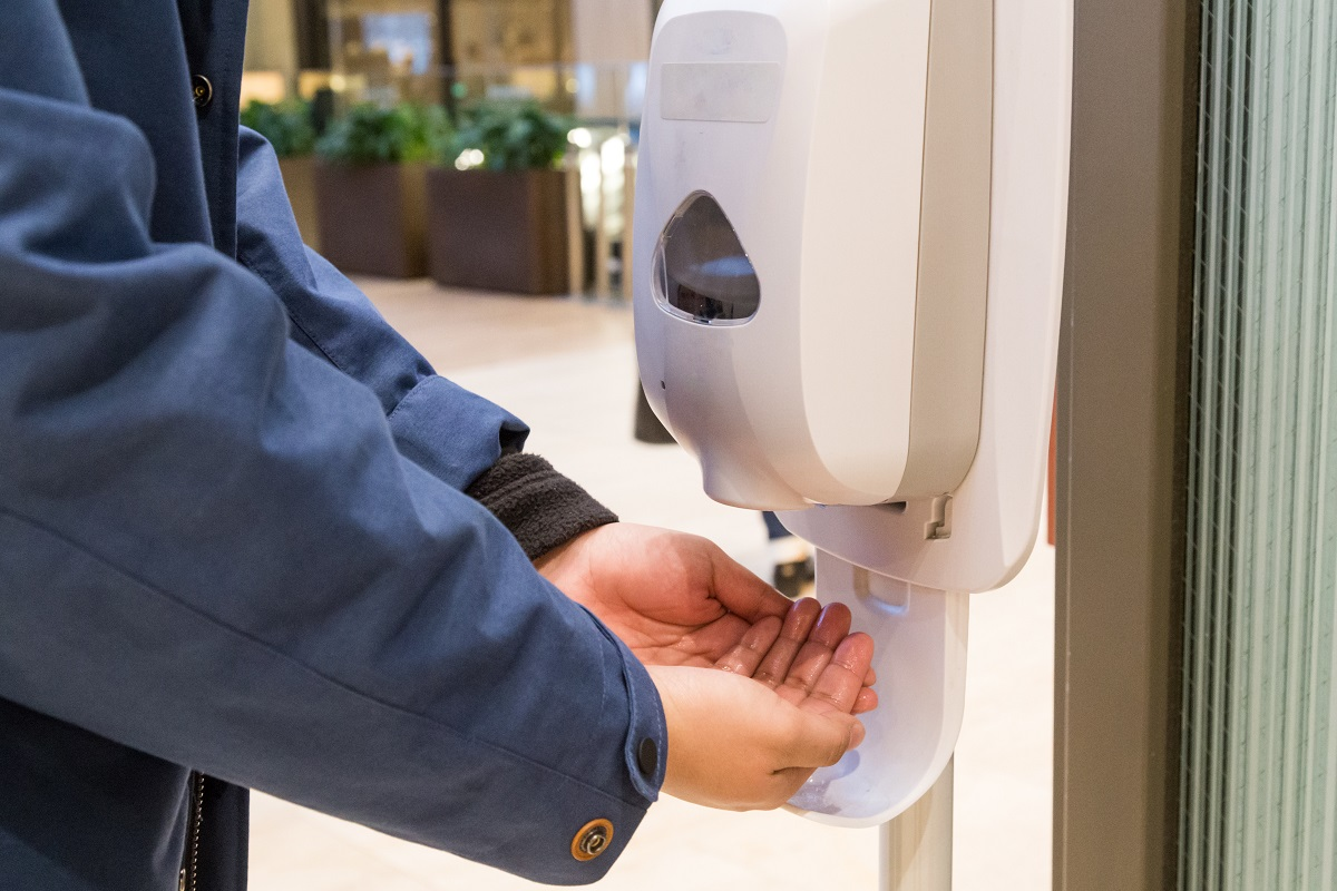 person getting hand sanitizer to clean their hands