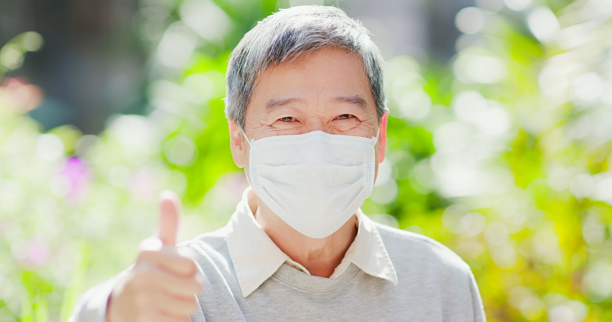 elderly man gives a thumbsup while wearing a mask