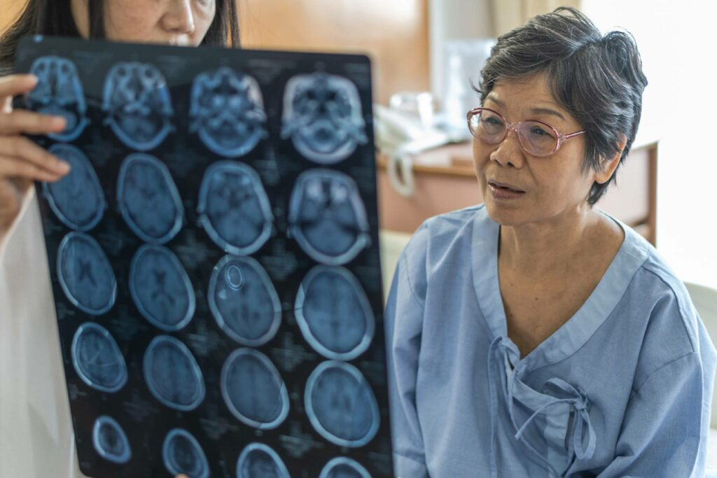 A senior woman looks at her brain scans with a doctor
