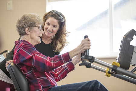A physical therapist helps an elderly woman with strength training exercises