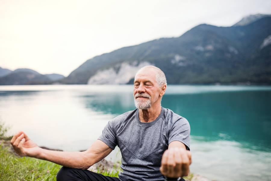 A senior man meditates in nature by a river and a mountain