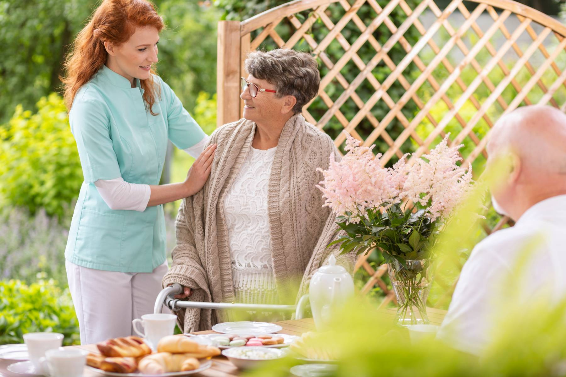 senior receiving help from a health care worker at an assisted living community