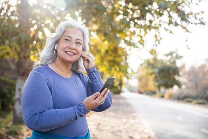 Older woman puts in her earbuds right before beginning her outdoor run